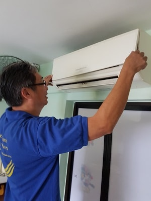 air conditioning service technician showing how to open aircon fan coil cover